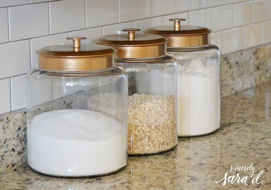 three clear canisters with gold lids hold flour, sugar, and oats