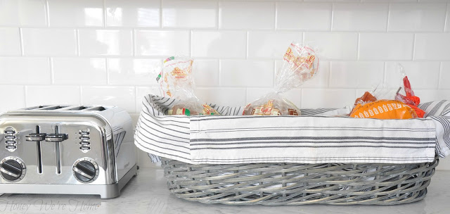 a grey wicker basket lined with a white towel holds three loaves of packaged bread