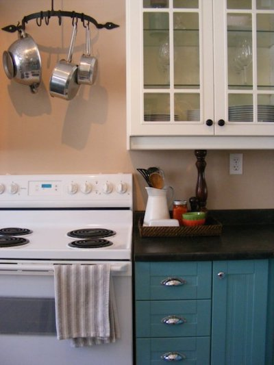 a hanging pot rack over a white kitchen stovetop