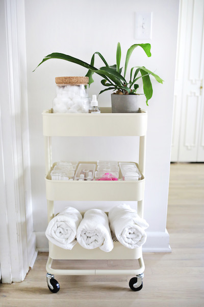 ikea raskog utility cart storing toiletries, a houseplant, towels, and more