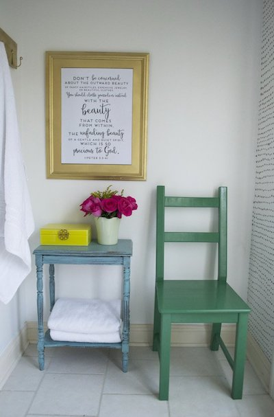 a poem in a gold picture frame above a blue side table next to a green chair in a bathroom