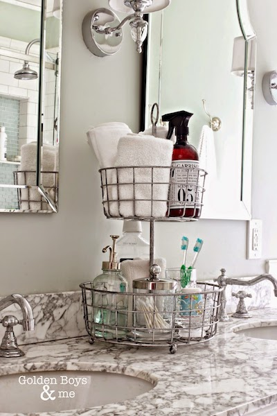 a two tiered wire basket organizer storing q-tips, toothbrushes, hand towels, mouth wash, and more