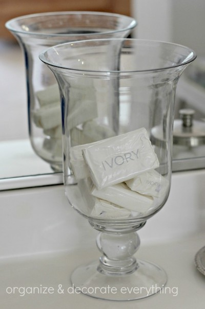 a hurricane glass on a bathroom counter storing bars of ivory soap
