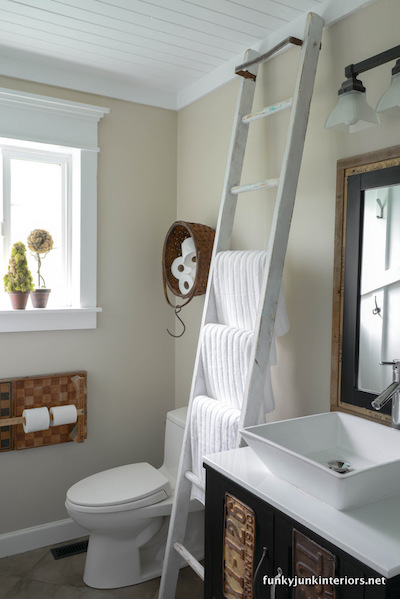 3 white towels on rungs of an old white ladder leaning against a bathroom wall