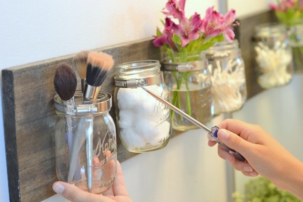 DIY mason jar organizers storing makeup brushes, cotton balls, flowers, and q-tips