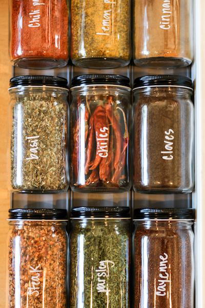 a spice drawer has been organized into uniform jars and labeled with a non-permanent marker