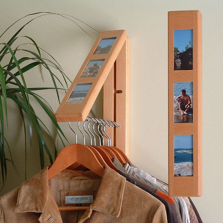 a clothes hanger pops out of a rebrilliant clothes hanging system, which looks like a photo frame hanging on the wall