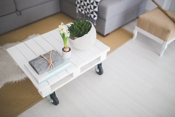 decluttered white wood pallet coffee table with wheels plants