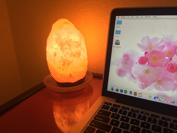 himalayan salt lamp next to a macbook on a table