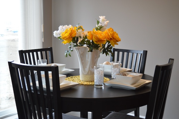 fresh white and yellow flowers in a white vase on a kitchen table