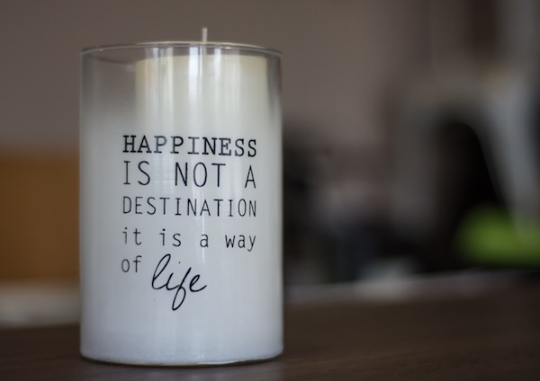 "white candle in a glass candle holder that reads ""happiness is not a destination it is a way of life"""