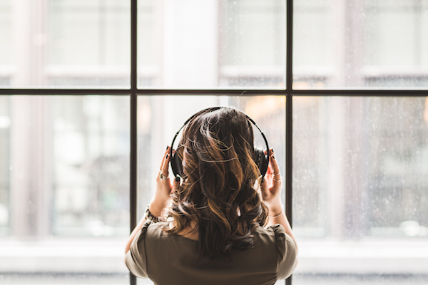 a woman wearing headphones looking out the window