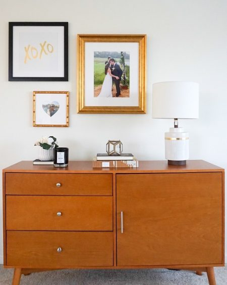 a classy gallery wall hangs above a large brown dresser
