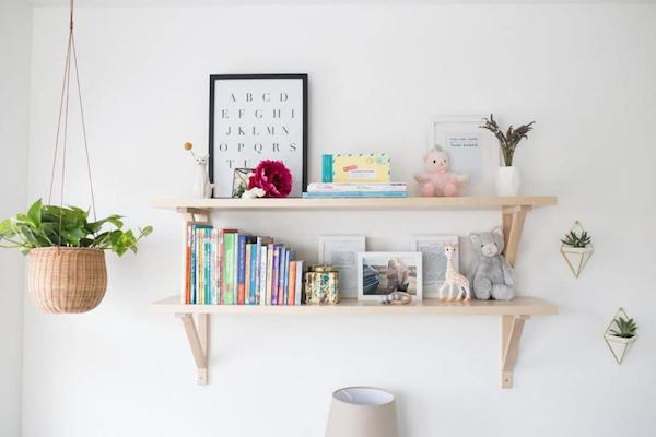 a white nursery with a pair of floating shelves