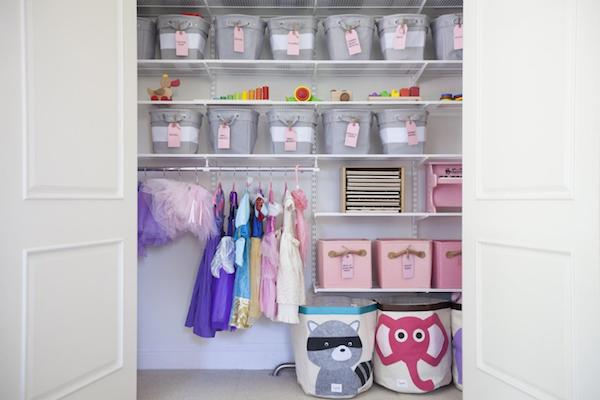 shelves in a play room hold bins of toys and play gear