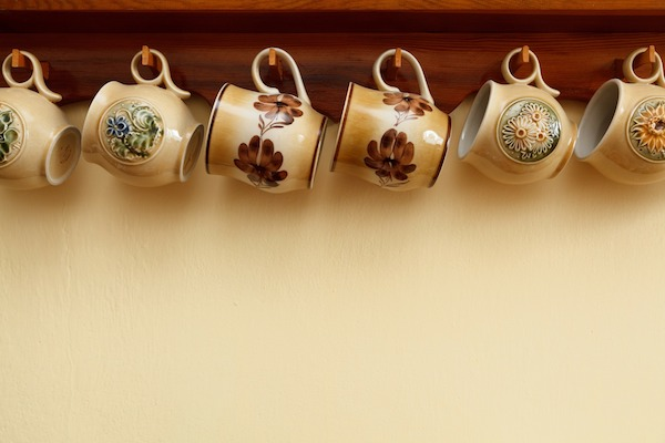 teacups hanging from under cabinet on hooks