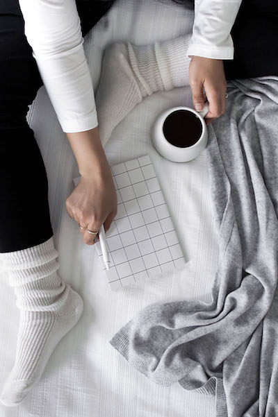 a woman sits on a bed with a mug of tea and a journal