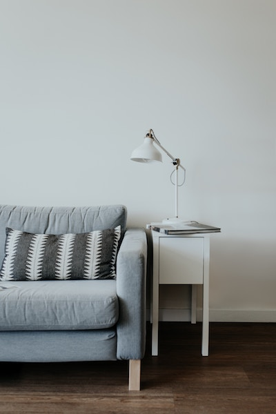 a nightstand and a couch in a white room