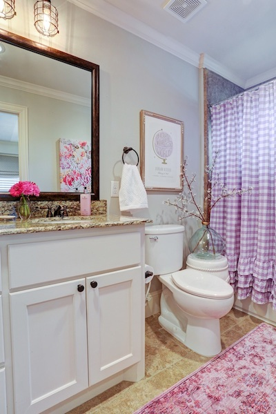 a perky bathroom with a pink shower curtain and flowers on the counter