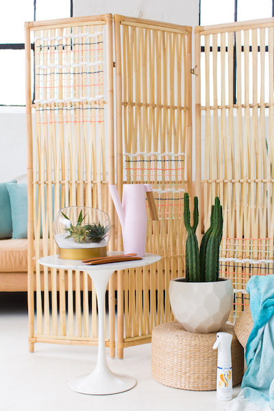 a bright rattan-woven folding screen divides a room in two