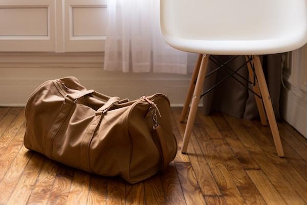 a canvas overnight bag lies next to a white chair