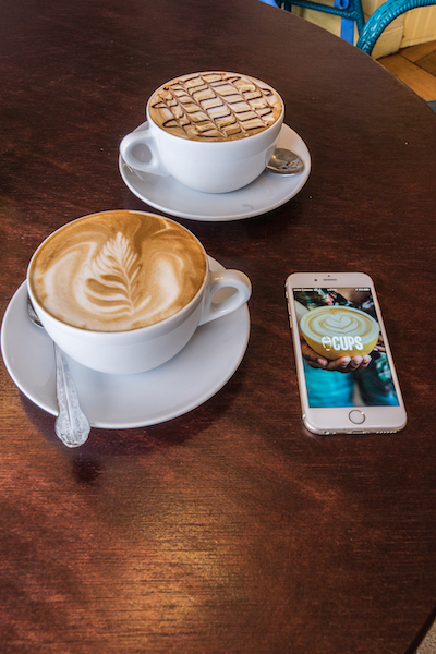 two delicious looking coffee drinks next to the app, Cups