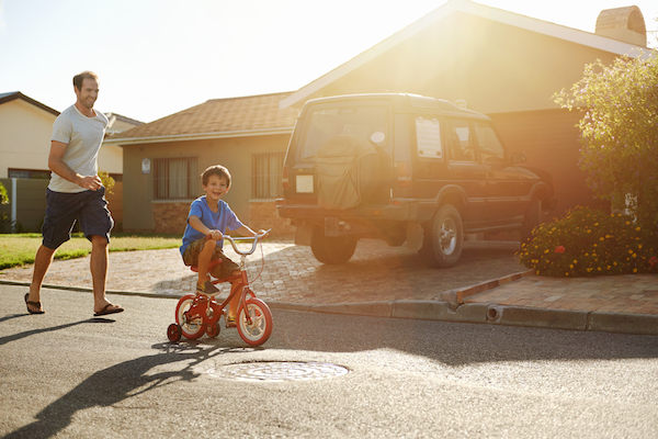 kid riding bike through neighborhood with dad