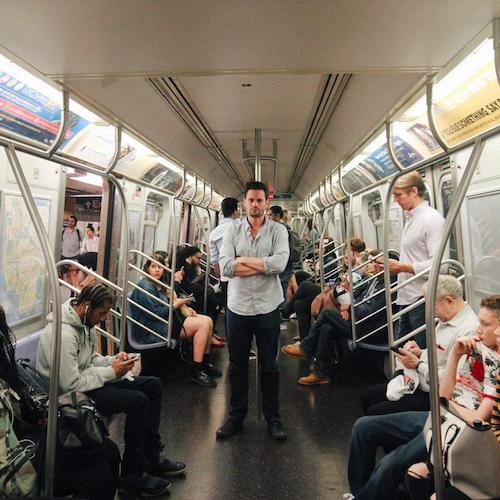Justin from Cool Cousin stands in the middle of a subway car