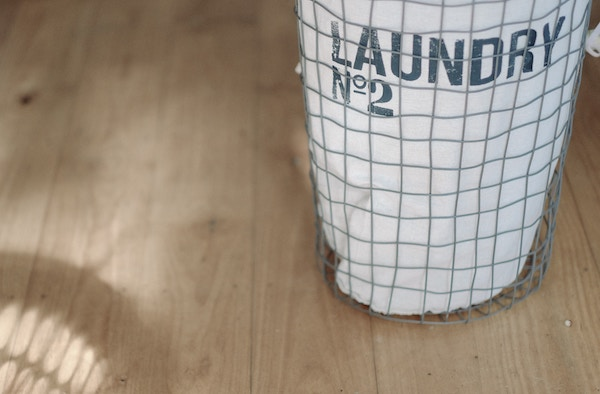 a laundry bag waits on the floor of a room