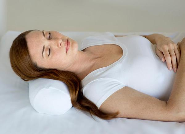 a woman lies down with a comfortable pillow in bed