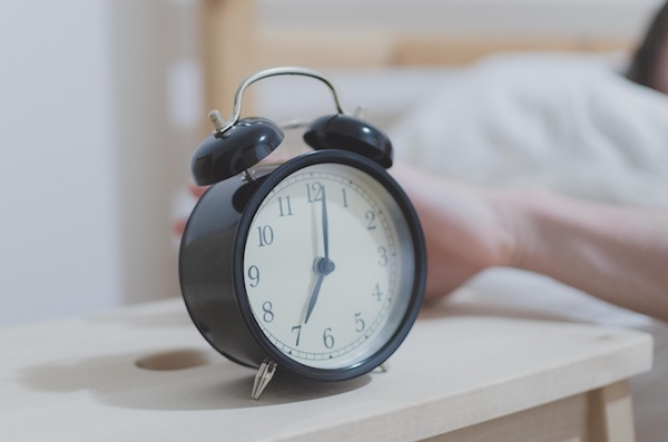 a hand reaches for the alarm clock in the morning
