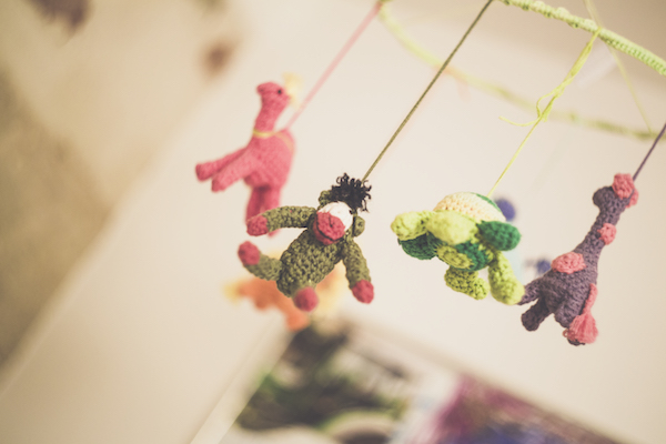 a mobile of friendly knit stuffed animals