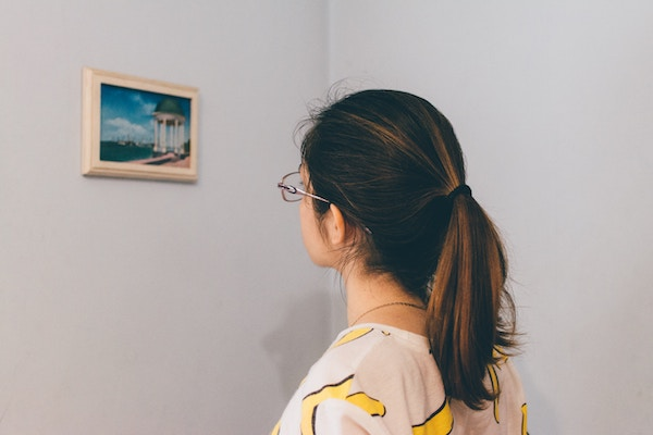 a woman approaches a work of art to examine it closer