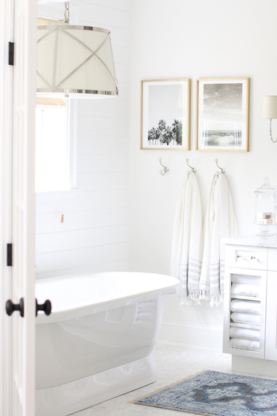 two tranquil art prints hang above turkish towels in a bathroom