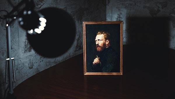 a lightbulb shines on a piece of art in a dark room