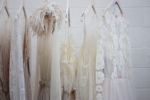 a row of wedding dress on a clothing rack