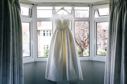 a single wedding dress hangs near a window