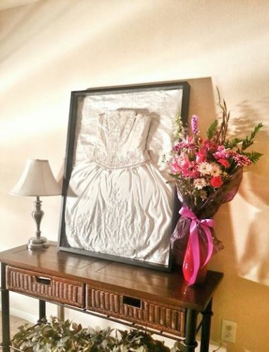 a framed wedding dress on an entryway table