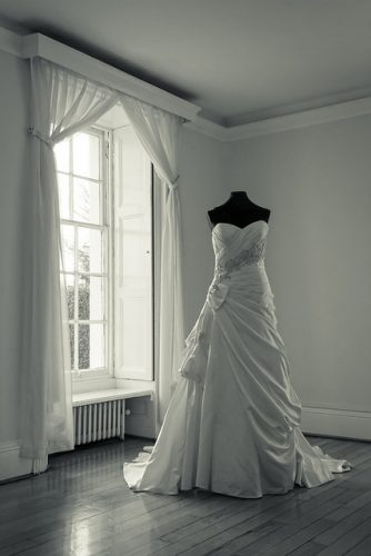 a wedding dress on a mannequin in an otherwise empty room