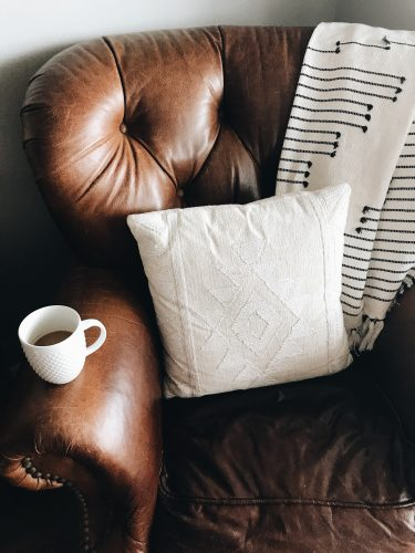 a comfy leather couch with a blanket