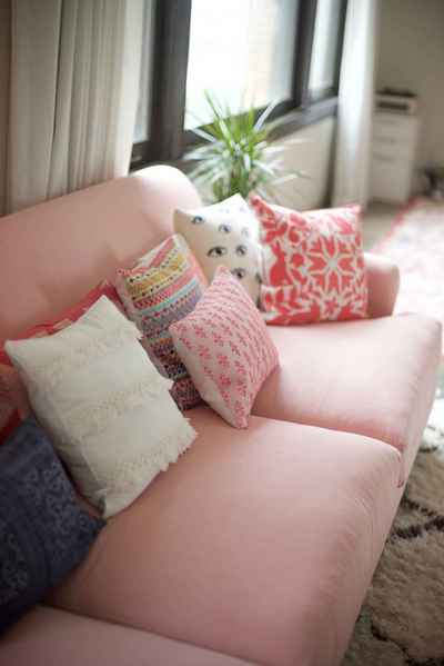 assorted throw pillows on pink sofa