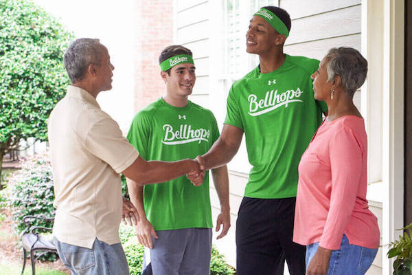 bellhops shaking hands with a customer