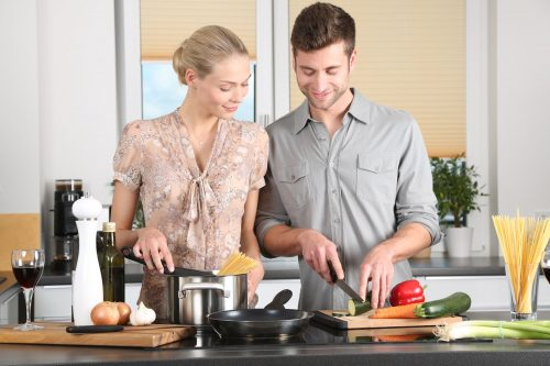 male and female couple cooking in the kitchen