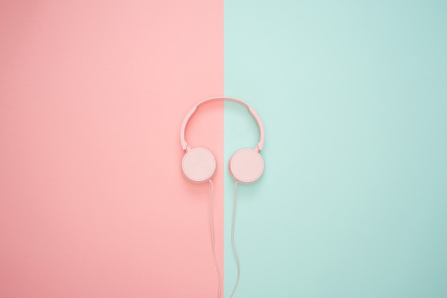 a pair of pink headphones by a blue and pink background