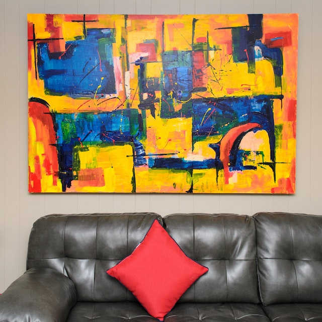 a bright abstract painting above a brown leather couch