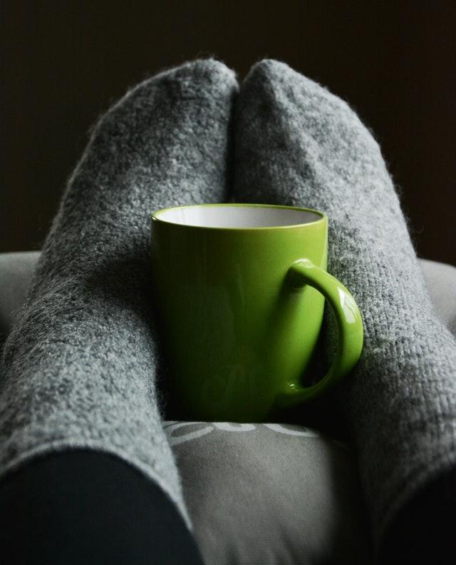 feet in warm fuzzy socks against a cup of warm beverage