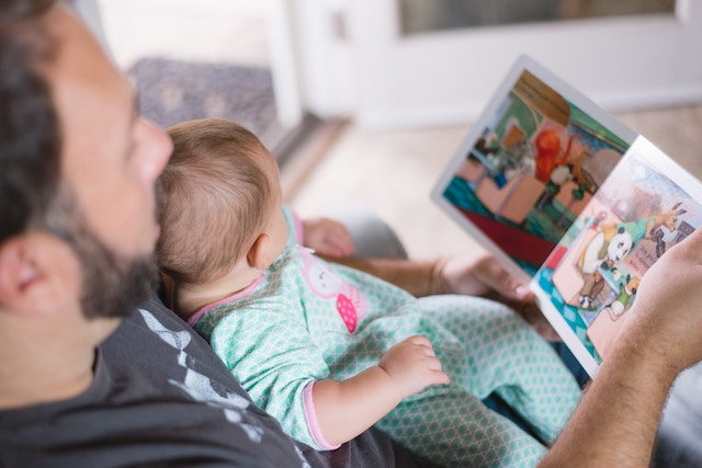 a parent reading to an infant