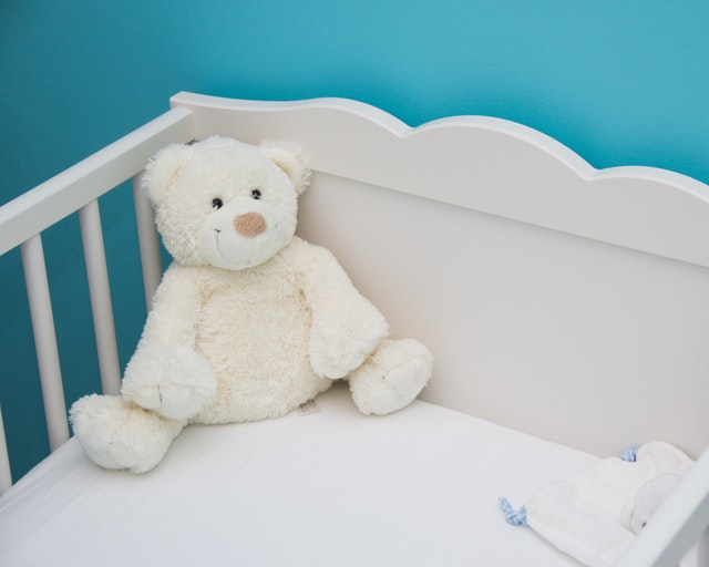 a white crib with a white stuffed bear