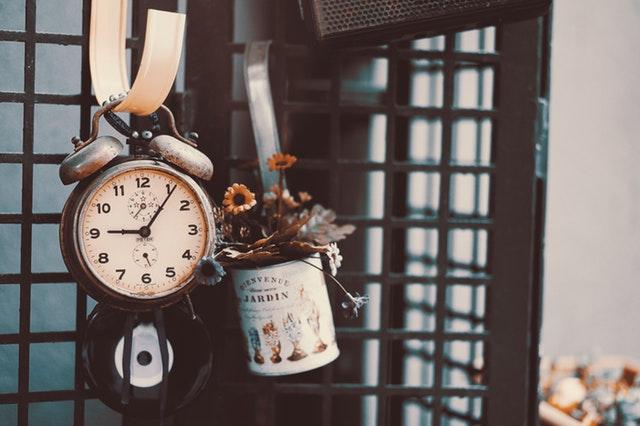 an antique clock hanging on a hook