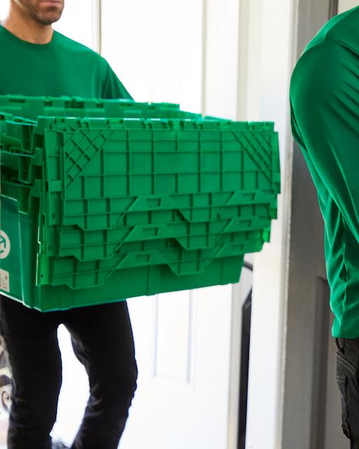 An individual carrying a MakeSpace bin